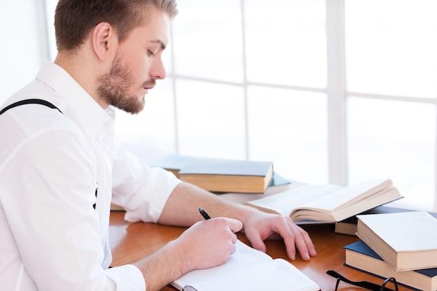 Zelfverzekerd en geïnspireerd. zijaanzicht van een zelfverzekerde jongeman in hemd en bretels die iets in een notitieblok schrijft terwijl hij aan tafel zit met boeken erop