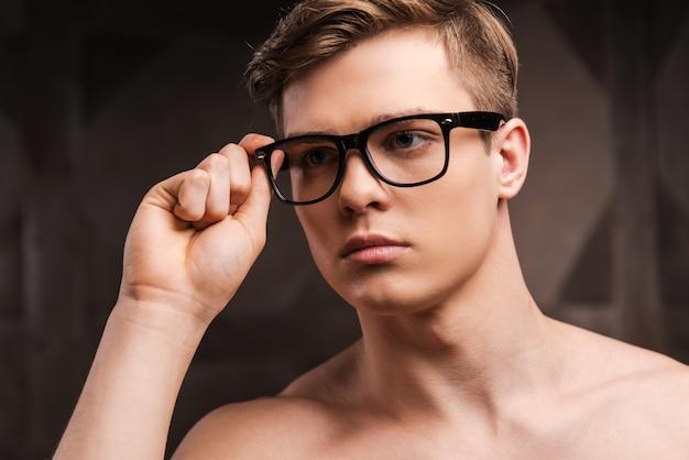 Zelfverzekerd en knap. knappe jonge man die zijn bril aanpast terwijl hij tegen een metalen achtergrond staat