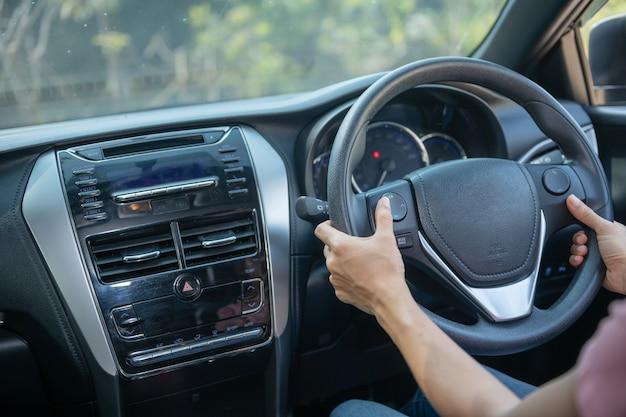 Zelfverzekerd en mooi. achteraanzicht van aantrekkelijke jonge vrouw in vrijetijdskleding die over haar schouder kijkt tijdens het autorijden. meisje met de hand op het wiel om de auto te hanteren, veiligheidsconcept.