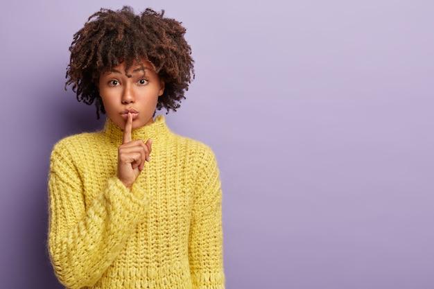 Zelfverzekerd ernstig vrouwelijk model met donkere huid, krullend haar, stilte gebaar maakt, geheim fluistert, roddels met vriend, gele gebreide trui draagt, stilte teken toont. lichaamstaal, samenzwering