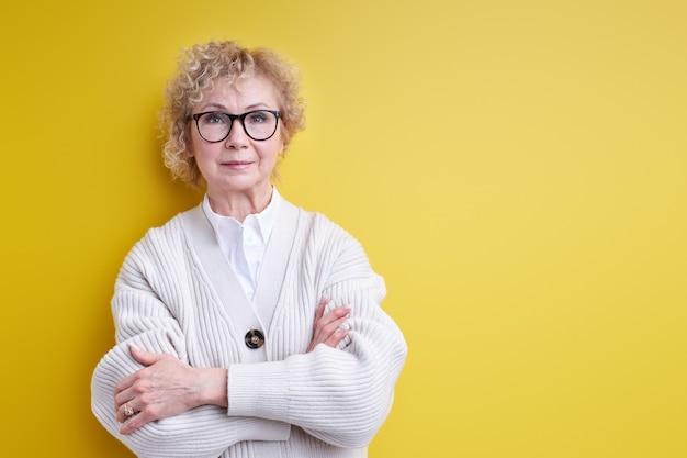 Zelfverzekerd ernstige rijpe vrouw poseren met gekruiste arm en front kijken