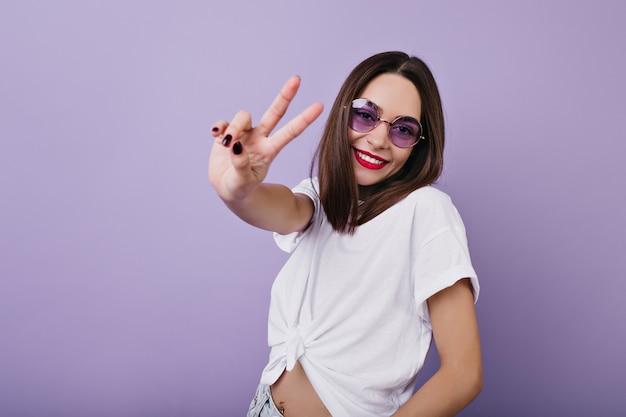 Zelfverzekerd europees meisje in ronde glazen poseren met vredesteken en glimlachen. indoor foto van elegante witte vrouw.
