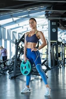 Zelfverzekerd fit meisje staat met gewichtsplaat op sportschool