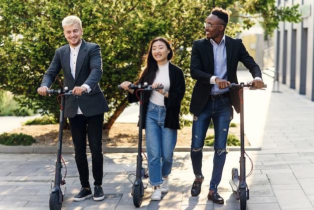 Zelfverzekerd gelukkig multiraciale collega's bespreken zakelijk project gaan in de buurt van kantoorgebouw met elektrische scooters