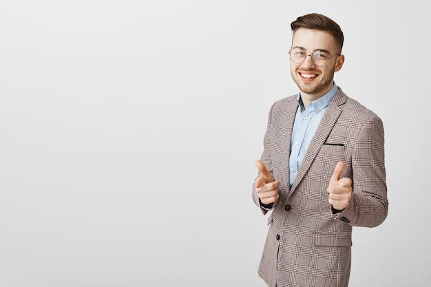 Zelfverzekerd gelukkig zakenman wijzende vinger pistolen en lachend tevreden, lof goed werk, complimenteer iemand, zeg gefeliciteerd