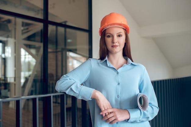Zelfverzekerd. gelukkig zelfverzekerde langharige vrouw in oranje veiligheidshelm en lichtblauwe blouse die staat met bouwplan binnenshuis