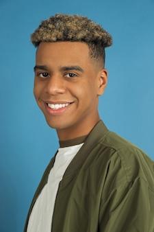Zelfverzekerd, glimlachend. sluit omhoog het portret van de afro-amerikaanse man dat op blauwe studioachtergrond wordt geïsoleerd. mooi mannelijk model in vrijetijdskleding. concept van menselijke emoties, gezichtsuitdrukking, verkoop, advertentie.