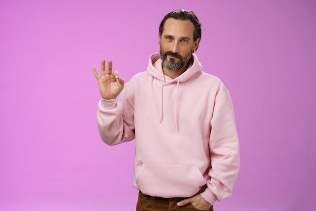 Zelfverzekerd goed uitziende gelukkige oude macho man met baard grijs haar in stijlvolle roze hoodie houden handzak toon oke ok goedkeuring gebaar grijnzend opgetogen eens dochter keuze, ondersteunend poseren.