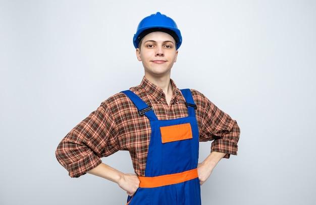 Zelfverzekerd handen op de hippe jonge mannelijke bouwer die uniform draagt