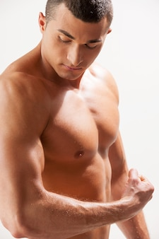 Zelfverzekerd in zijn perfecte lichaam. knappe jonge gespierde man die zijn spieren onderzoekt terwijl hij tegen een grijze achtergrond staat
