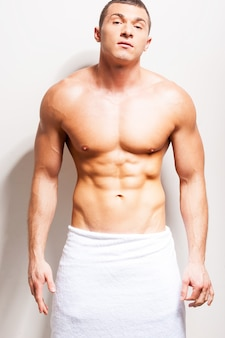 Zelfverzekerd in zijn perfecte lichaam. zelfverzekerde jonge shirtloze man bedekt met een handdoek die naar de camera kijkt terwijl hij tegen een grijze achtergrond staat