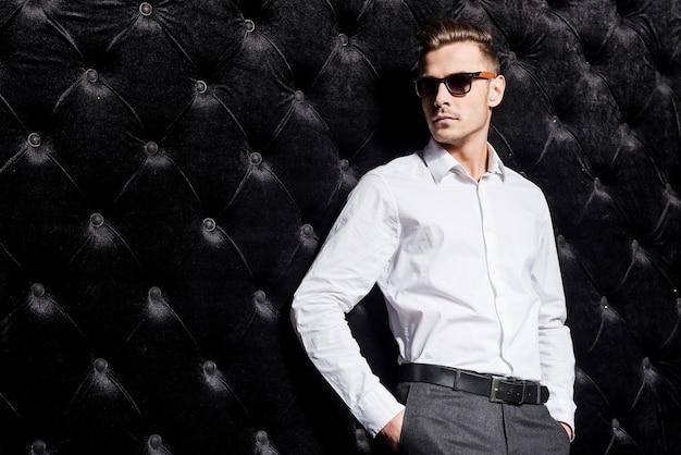 Zelfverzekerd in zijn stijl. knappe jonge man in wit overhemd hand in hand in zakken en wegkijkend terwijl hij tegen een zwarte achtergrond staat