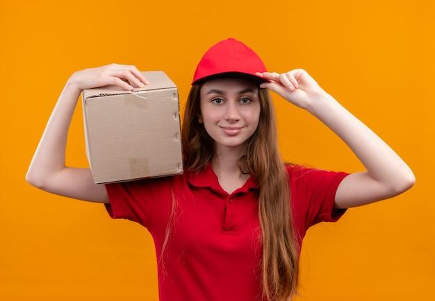Zelfverzekerd jong bezorgmeisje in een rode uniforme doos op de schouder houden en de hand op de dop zetten op geïsoleerde oranje ruimte