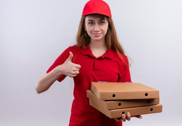 Zelfverzekerd jong bezorgmeisje in rode uniforme bedrijfspakketten en duim opdagen op geïsoleerde witte ruimte