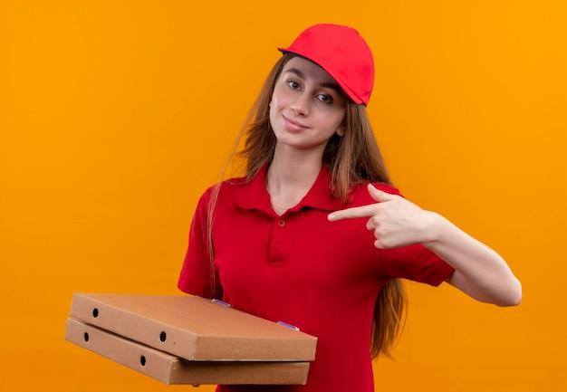 Zelfverzekerd jong bezorgmeisje in rode uniforme bedrijfspakketten en wijzend op hen op geïsoleerde oranje ruimte