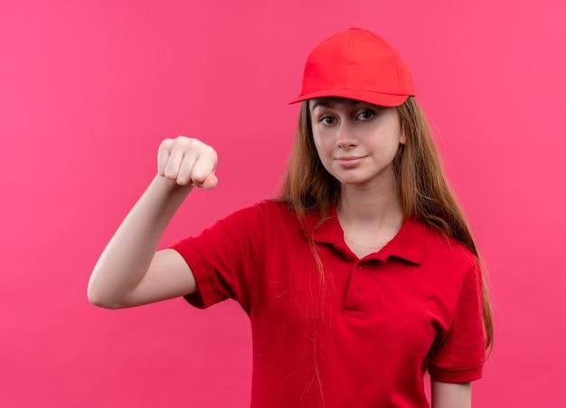 Zelfverzekerd jong bezorgmeisje in rood uniform doet klopgebaar op geïsoleerde roze ruimte