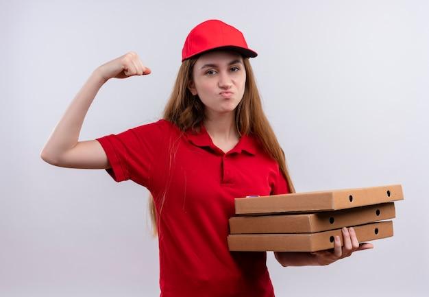 Zelfverzekerd jong bezorgmeisje in rood uniform doet sterk gebaar en houdt pakketten op geïsoleerde witte ruimte