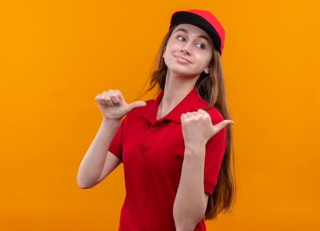 Zelfverzekerd jong bezorgmeisje in rood uniform duimen opdagen aan de rechterkant op geïsoleerde oranje ruimte met kopie ruimte