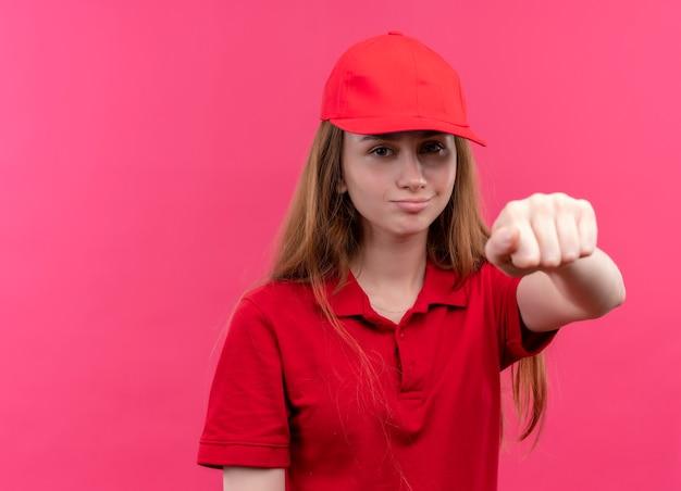 Zelfverzekerd jong bezorgmeisje in rood uniform haar vuist uitrekken op geïsoleerde roze ruimte met kopie ruimte