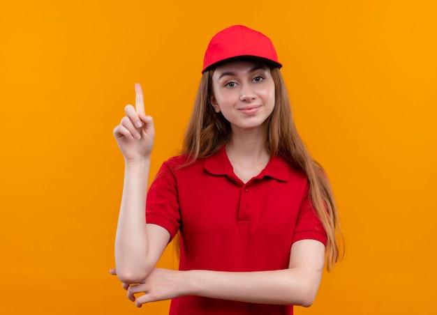 Zelfverzekerd jong bezorgmeisje in rood uniform met opgeheven vinger op geïsoleerde oranje ruimte