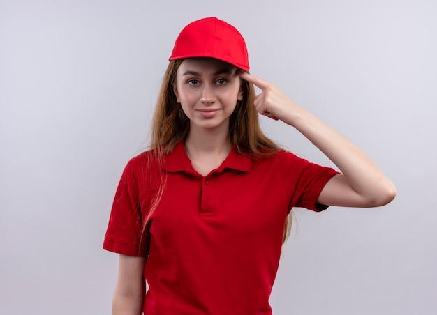 Zelfverzekerd jong bezorgmeisje in rood uniform vinger zetten tempel op geïsoleerde witte ruimte