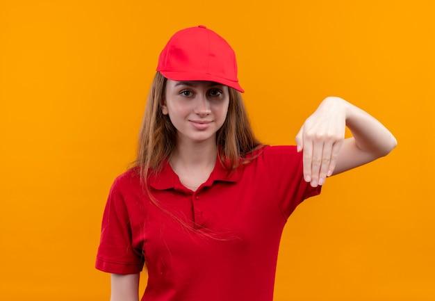 Zelfverzekerd jong bezorgmeisje in rood uniform wijzend met hand naar beneden op geïsoleerde oranje ruimte
