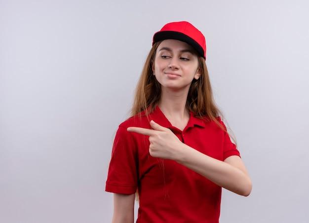 Zelfverzekerd jong bezorgmeisje in rood uniform wijzend naar de linkerkant op geïsoleerde witte ruimte met kopie ruimte
