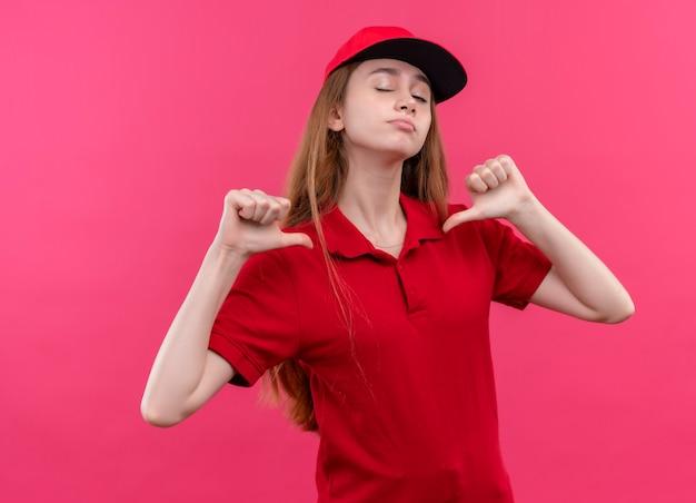 Zelfverzekerd jong bezorgmeisje in rood uniform wijzend op zichzelf en knipogen op geïsoleerde roze ruimte