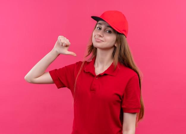 Zelfverzekerd jong bezorgmeisje in rood uniform wijzend op zichzelf op geïsoleerde roze ruimte