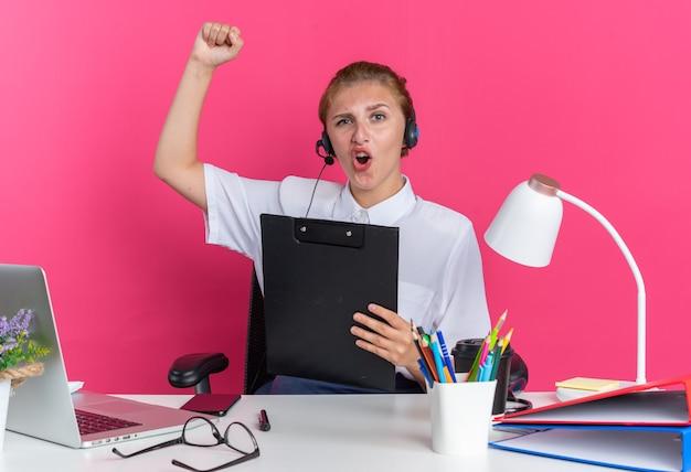 Zelfverzekerd jong blond callcenter meisje met hoofdtelefoon zittend aan een bureau met uitrustingsstukken met klembord kijkend naar camera doen ja gebaar geïsoleerd op roze muur