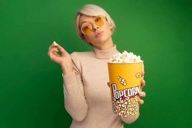 Zelfverzekerd jong blond meisje met een zonnebril die een emmer popcorn uitrekt en popcornstukken vasthoudt die op een groene muur met kopieerruimte zijn geïsoleerd