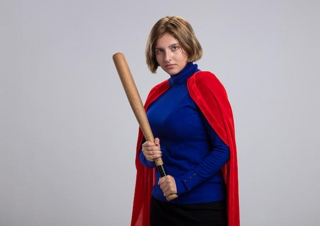 Zelfverzekerd jong blond superheldmeisje in rode cape die zich in profielmening bevinden die honkbalknuppel houden die op witte muur met exemplaarruimte wordt geïsoleerd