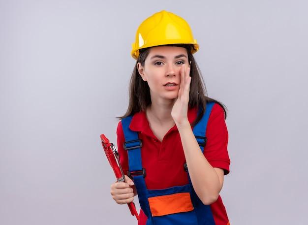 Zelfverzekerd jong bouwersmeisje houdt bouwbenodigdheden vast en beweert iemand op geïsoleerde witte achtergrond met exemplaarruimte te bellen
