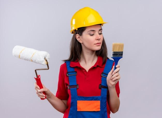 Zelfverzekerd jong bouwersmeisje houdt verfroller en kwast op geïsoleerde witte achtergrond