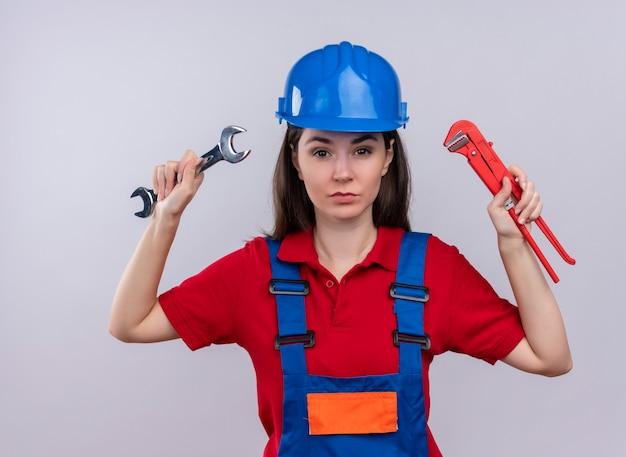 Zelfverzekerd jong bouwersmeisje houdt workshopsleutel en waterpomptang op geïsoleerde witte achtergrond