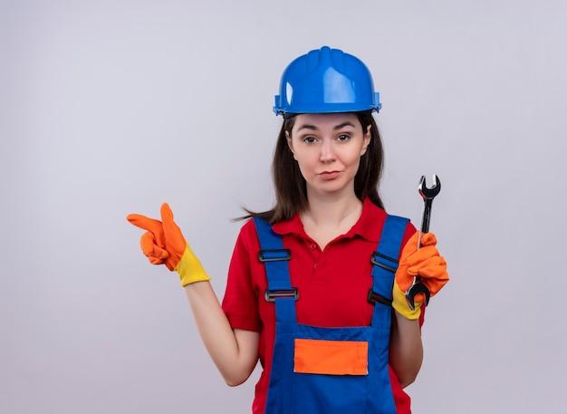 Zelfverzekerd jong bouwersmeisje houdt workshopsleutel en wijst naar de kant op geïsoleerde witte achtergrond