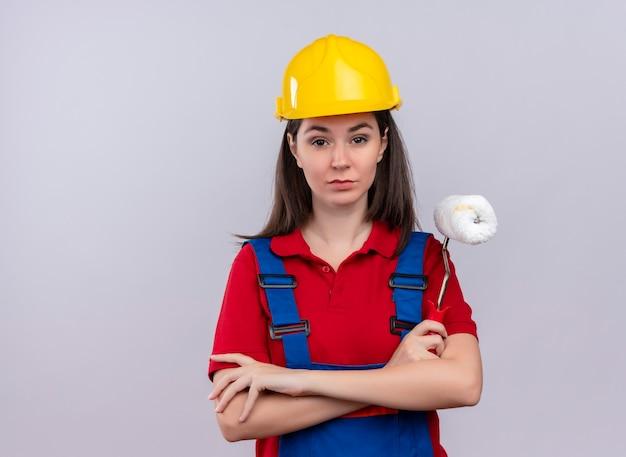 Zelfverzekerd jong bouwersmeisje kruist armen en houdt verfroller op geïsoleerde witte achtergrond met kopie ruimte