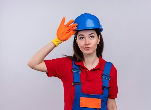 Zelfverzekerd jong bouwersmeisje legt hand op veiligheidshelm op geïsoleerde witte achtergrond