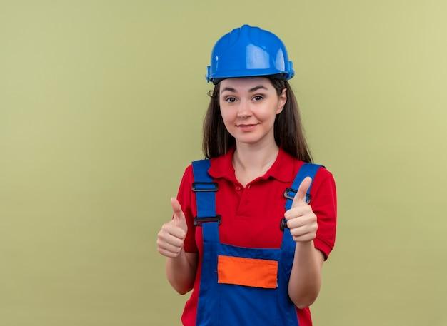 Zelfverzekerd jong bouwersmeisje met blauwe veiligheidshelm duimen omhoog met beide handen op geïsoleerde groene achtergrond met exemplaarruimte