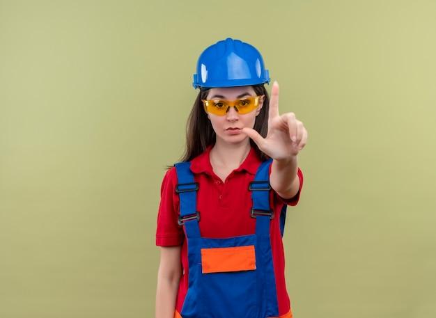Zelfverzekerd jong bouwersmeisje met blauwe veiligheidshelm en met veiligheidsbril houdt hand omhoog op geïsoleerde groene achtergrond met exemplaarruimte