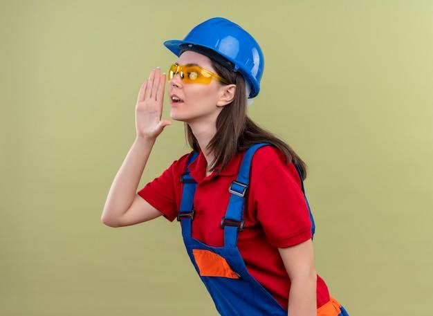 Zelfverzekerd jong bouwersmeisje met blauwe veiligheidshelm en met veiligheidsbril kijkt naar de zijkant en beweert iemand te bellen op geïsoleerde groene achtergrond