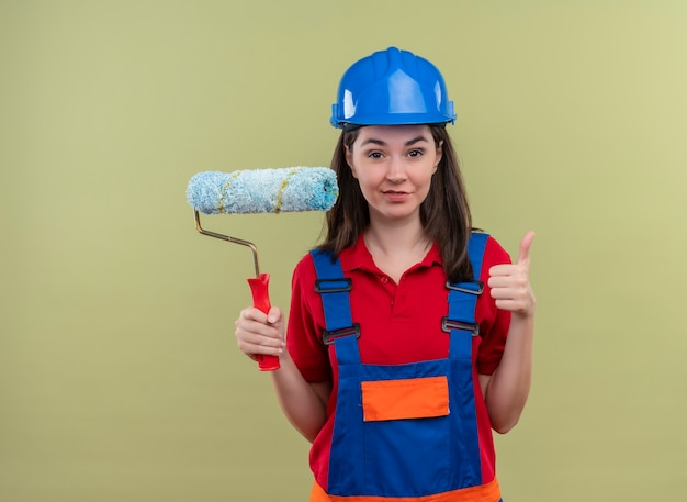Zelfverzekerd jong bouwersmeisje met blauwe veiligheidshelm houdt verfroller en duimen omhoog op geïsoleerde groene achtergrond met kopie ruimte