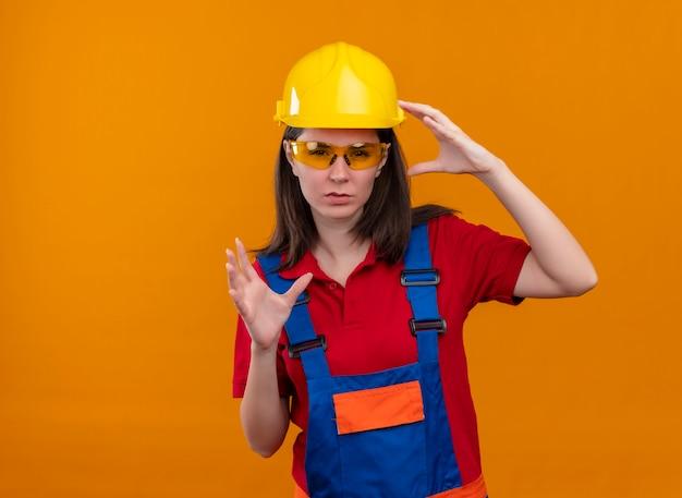 Zelfverzekerd jong bouwersmeisje met veiligheidsbril houdt handen omhoog op geïsoleerde oranje achtergrond met exemplaarruimte