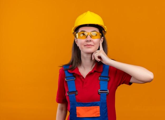 Zelfverzekerd jong bouwersmeisje met veiligheidsbril legt hand op kin en kijkt omhoog op geïsoleerde oranje achtergrond met exemplaarruimte