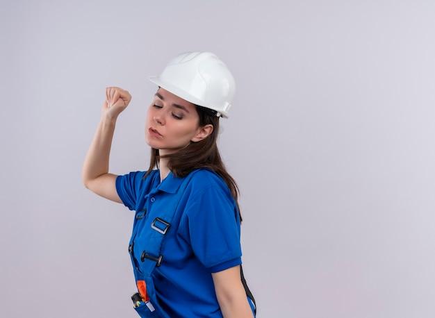 Zelfverzekerd jong bouwersmeisje met witte veiligheidshelm en blauw uniform dansen en houdt vuist omhoog op geïsoleerde witte achtergrond met exemplaarruimte
