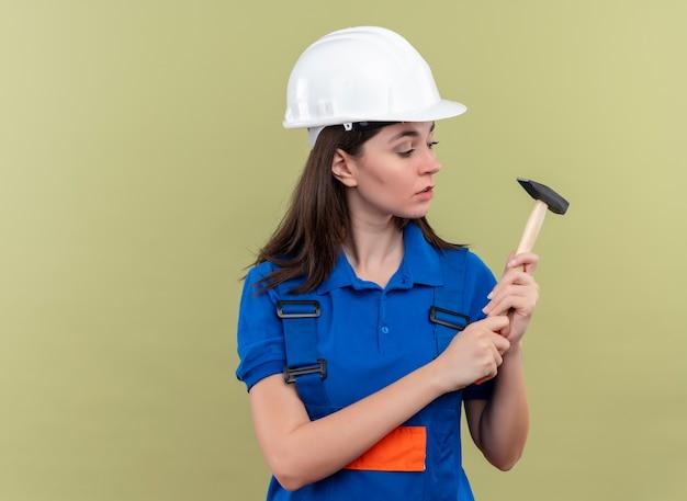 Zelfverzekerd jong bouwersmeisje met witte veiligheidshelm en blauw uniform houdt hamer en bekijkt hamer op geïsoleerde groene achtergrond met exemplaarruimte