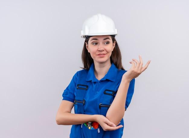 Zelfverzekerd jong bouwersmeisje met witte veiligheidshelm en blauw uniform houdt hand omhoog op geïsoleerde witte achtergrond met exemplaarruimte