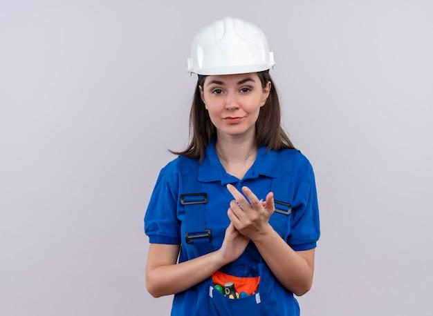 Zelfverzekerd jong bouwersmeisje met witte veiligheidshelm en blauw uniform klapt in handen op geïsoleerde witte achtergrond met exemplaarruimte