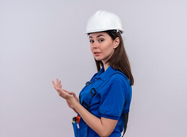Zelfverzekerd jong bouwersmeisje met witte veiligheidshelm en blauw uniform staat zijwaarts en klapt in handen op geïsoleerde witte achtergrond met exemplaarruimte