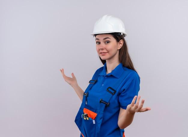 Zelfverzekerd jong bouwersmeisje met witte veiligheidshelm en blauw uniform staat zijwaarts met handen omhoog op geïsoleerde witte achtergrond met exemplaarruimte